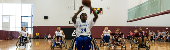 Youth wheelchair basketball player shoots with other players looking on